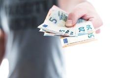 Ręka wręcza nad euro banknotami męska osoba obraz royalty free