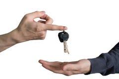 Ręka wręcza nad samochodów kluczami z palca i ręki dostawaniem Zdjęcia Stock