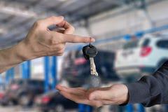 Ręka wręcza nad samochodów kluczami z palca i ręki dostawaniem na gar Obrazy Royalty Free