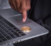 Ręka wskazuje złotego bitcoin z laptopem zdjęcia stock