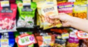 Ręka wybiera słodkich produkty lub bierze kobieta, przekąski na shelv Zdjęcia Stock
