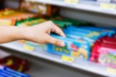 Ręka wybiera słodkich produkty lub bierze kobieta, przekąski na shelv Zdjęcie Royalty Free