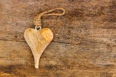 Ręka wykonywał ręcznie drewnianego serce z arkaną wieszać na szorstkim wietrzejącym w Zdjęcie Royalty Free
