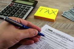 Ręka wypełnia podatek formę 1040 przeciw tłu dolary i kalkulator fotografia royalty free
