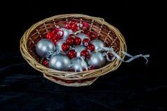 Ręka wyplatający łozinowy kosz wypełniał z Bożenarodzeniowymi ornamentami na czarnym tle fotografia stock