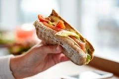 Ręka z łososiową panini kanapką przy restauracją Zdjęcie Royalty Free