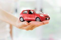 Ręka z czerwonym samochodem dealership zdjęcia royalty free