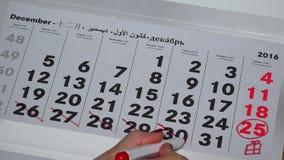 Ręka z czerwonymi markiera zwłoki kopyto_szewski dniami Grudnia miesiąc 2016 rok kalendarz zbiory