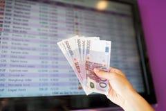 Ręka z euro pieniądze nad wymian walut tempami Obraz Royalty Free