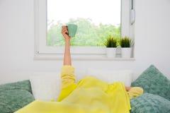 Ręka z filiżanką w łóżku zdjęcie stock