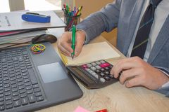 Ręka z kalkulatorem Finanse i księgowości biznes Młody biznesmen Kalkuluje Finansowych rachunki W biurze Obraz Royalty Free