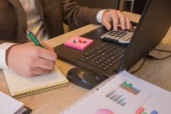 Ręka z kalkulatorem Finanse i księgowości biznes Młody biznesmen Kalkuluje Finansowych rachunki W biurze Fotografia Royalty Free