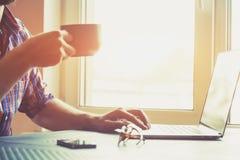 Ręka z laptopem i filiżanką herbata lub kawa Zdjęcia Stock