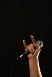 Ręka z mikrofonem i diabłem uzbrajać w rogi odosobnionego na czerni Obraz Royalty Free