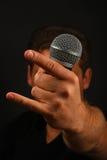 Ręka z mikrofonem i diabłem uzbrajać w rogi odosobnionego na czerni Obrazy Royalty Free