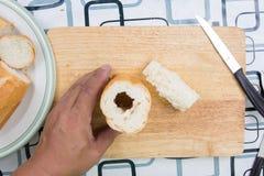 Ręka z nożem penetruje chleb obrazy stock