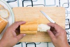 Ręka z nożem penetruje chleb fotografia stock