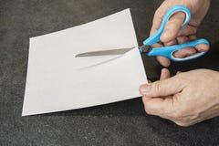 Ręka z nożycami ciie papier zdjęcie stock