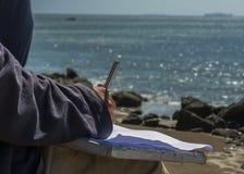 Ręka z ołówkiem przed morzem Zdjęcie Royalty Free