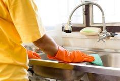 Ręka z pomarańczowego rękawiczkowego cleaning Kuchennym zlew Zdjęcie Stock
