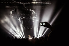 Ręka z smartphone nagrywa muzyka na żywo festiwal, Bierze fotografię koncertowa scena Obrazy Stock