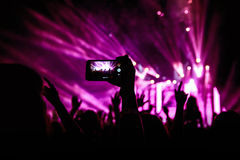 Ręka z smartphone nagrywa muzyka na żywo festiwal, Bierze fotografię koncertowa scena Zdjęcie Stock