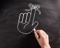 Ręka z Tasiemkowym rysunkiem na Czarnym Chalkboard zdjęcia royalty free