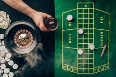 Ręka z whisky w szkle kasyno stołem z zakładami zdjęcia stock