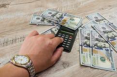 Ręka z wristwatch, kalkulatorem i dolarami na drewnianym tle, zdjęcia royalty free
