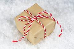 Ręka zawijał prostego papieru prezenta małego pudełko wiążącego z czerwonym i białym Fotografia Stock