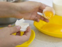 Ręki łamają surowego jajko Rozdzielenie jajeczny biel od yolk Zdjęcia Royalty Free