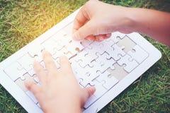 Ręki łamigłówki złączeni kawałki na zielonej trawy tle Zdjęcia Royalty Free
