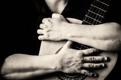 Ręki ściska gitarę akustyczną obraz royalty free