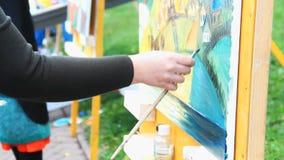Ręki żeński artysty obrazu obrazek na sztaludze outdoors zbiory