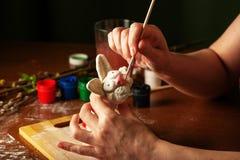 Ręki artysta malują Wielkanocnego królika Akwarela maluje w słojach i tubkach handwork zdjęcie stock