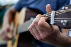 Ręki bawić się gitarę akustyczną Obrazy Stock