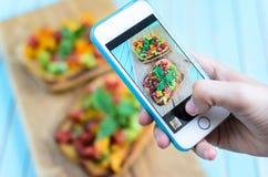 Ręki bierze fotografię z smartphone bruschetta na drewnianej tnącej desce Obrazy Royalty Free