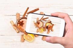 Ręki bierze fotografia rozmyślającego wino z smartphone Zdjęcia Stock