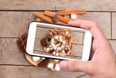 Ręki bierze fotografii gorącego kakao z smartphone fotografia royalty free
