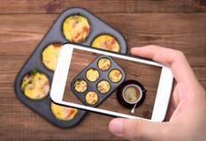 Ręki bierze fotografii jajecznych muffins i filiżankę kawy z smartphone Obrazy Stock