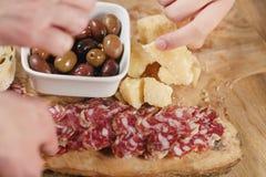 Ręki bierze włoskie antipasti zakąski na stole Obraz Stock