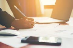 Ręki biznesowej kobiety pieniężny kierownik bierze notatki gdy praca Obrazy Royalty Free