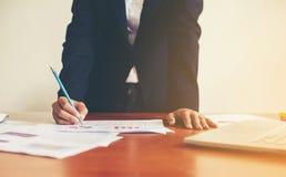Ręki biznesowej kobiety pieniężny kierownik bierze notatki gdy praca Zdjęcie Stock