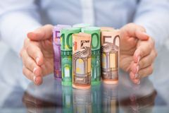 Ręki chronienie staczający się w górę euro banknotu Obraz Royalty Free
