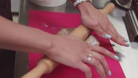 Ręki ciasto szef kuchni używa tocznej szpilki na cieście na różową tnącą deskę zdjęcie wideo