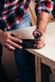 Ręki cieśla planowali drewno, miejsce pracy Zdjęcia Royalty Free