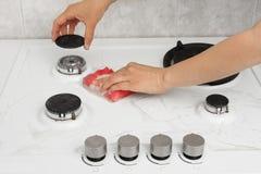 Ręki czyści benzynową kuchenkę z gąbką Obrazy Royalty Free