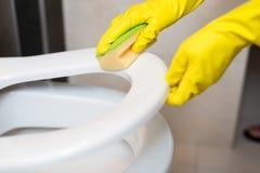 Ręki czyści toaletowego siedzenia w wc z żółtą gąbką Zdjęcia Stock