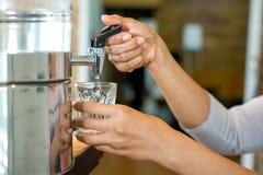 Ręki dolewania woda rozjaśniać szkło wewnątrz Obraz Stock