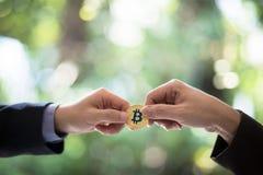 Ręki dwa biznesmena handlują monetę bitcoin Symboliczne monety bitcoin elektronicznego pieniądze wymiana, biznes, Obraz Royalty Free